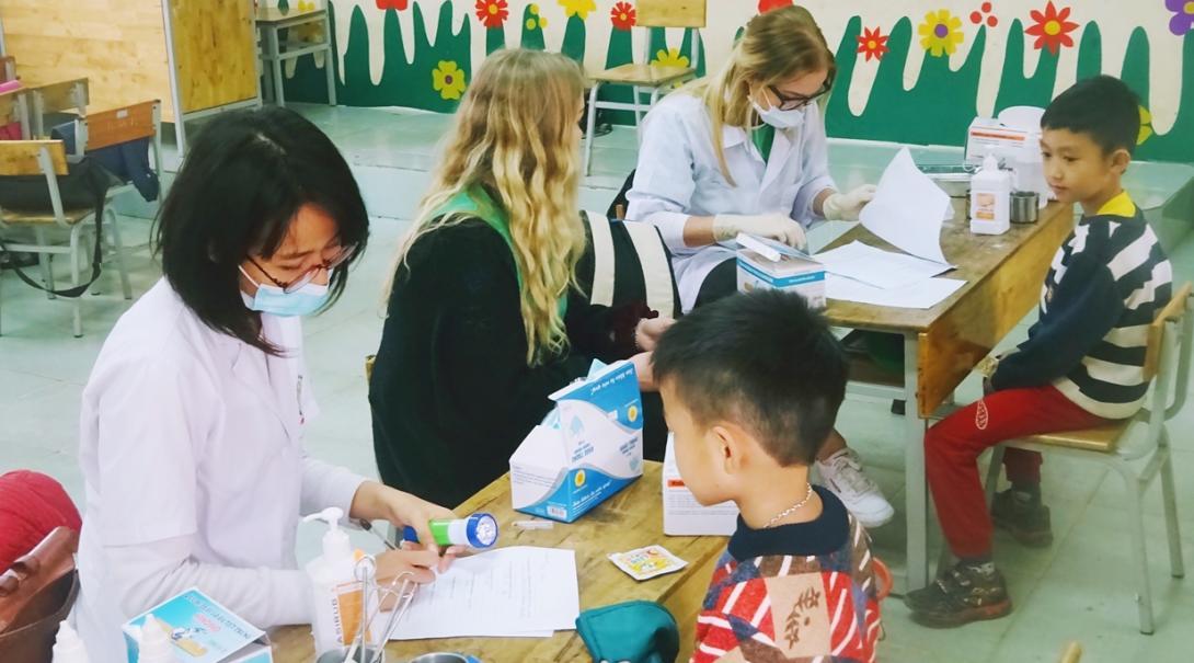 ベトナムの学校でヘルスチェックを行う看護インターンたち